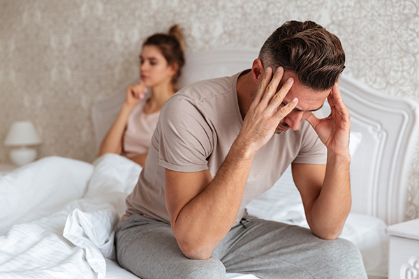 Sad man sitting on bed with his girlfriend on background